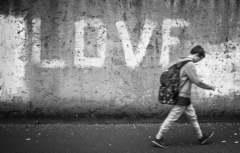 Schoolboy with backpack. Schoolboy walking down the street with head bowed; love on background. Back to school stock images