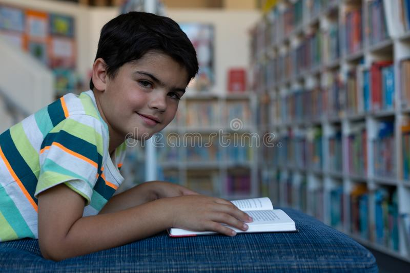 Schoolboy with book looking at camera in library royalty free stock image