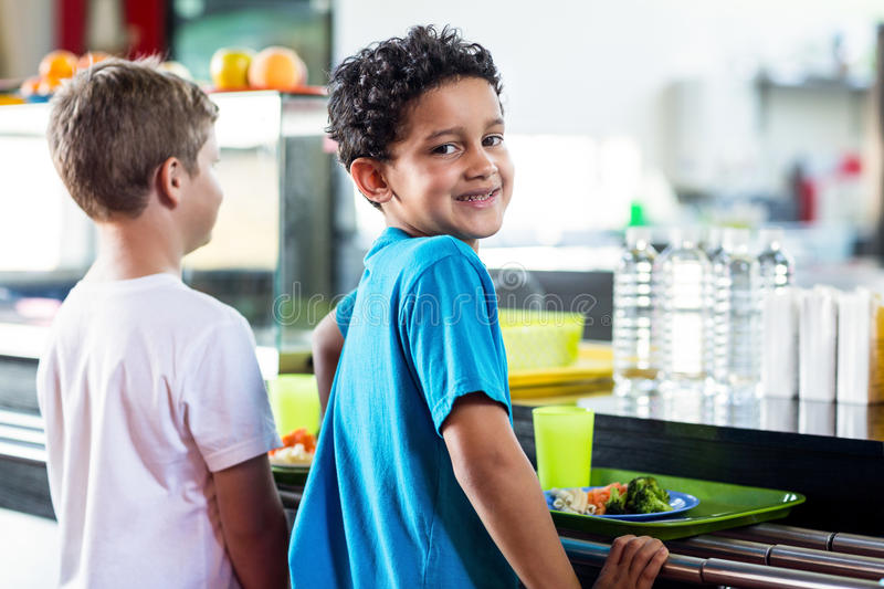 Schoolboy with classmate standing near canteen counter. Portrait of smiling schoolboy with classmate standing near canteen counter royalty free stock photography