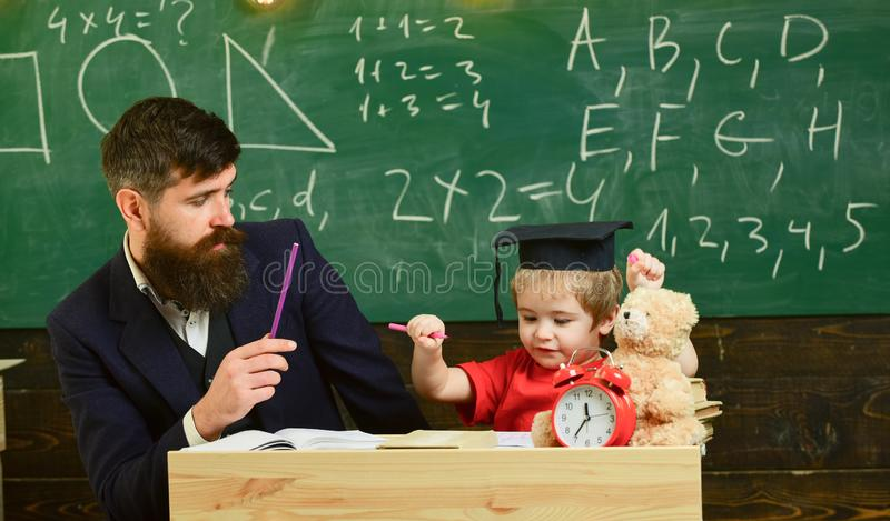 Schoolboy doing hometask with father and writting in workbook, chalkboard on background. Father checking hometask, helps. To boy, son. Hometask concept royalty free stock photo