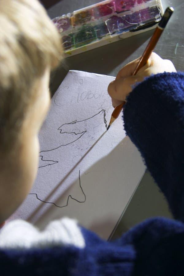 Schoolboy drawing stock photo