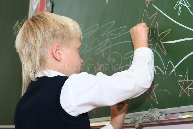 The schoolboy draws on a school board royalty free stock image