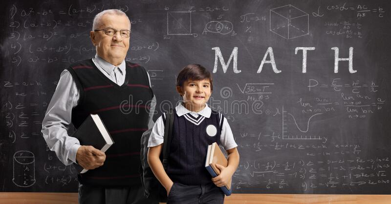 Schoolboy and an elderly male teacher posing in front of a blackboard with written text math and formulas stock images