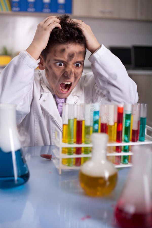 Schoolboy Experiment in the school lab. Funny crazy scientist boy working in laboratory stock photography