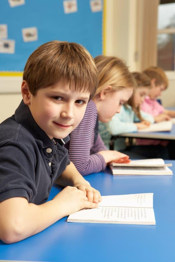 schoolboy för bokklassrumavläsning royaltyfri fotografi