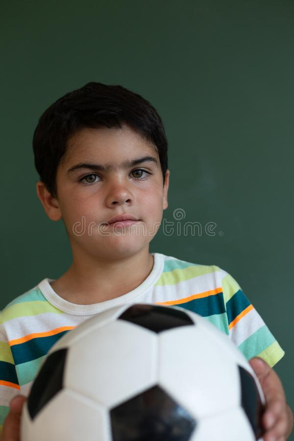 Schoolboy with football standing in classroom royalty free stock images