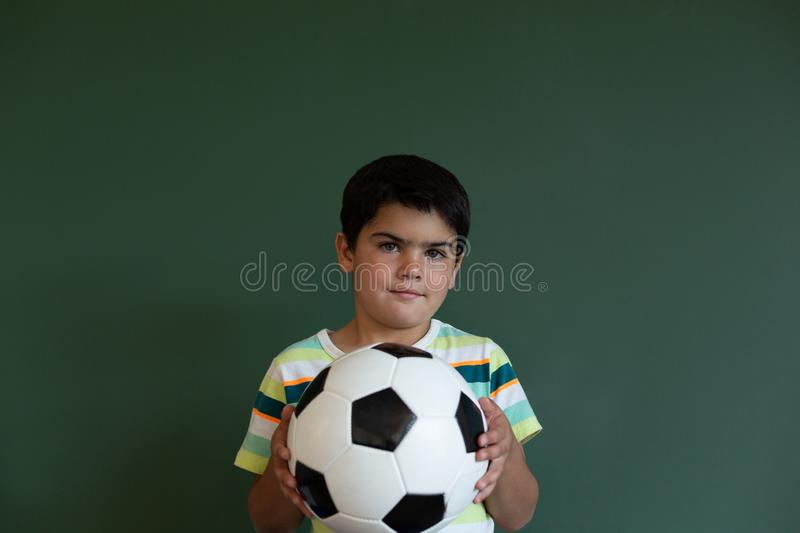 Schoolboy with football standing in classroom stock image