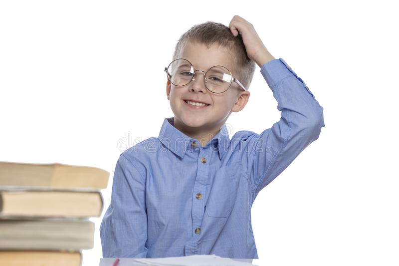 A schoolboy with glasses sits at a table and laughs. Isolated over white background stock image