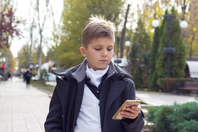 Schoolboy habillé de vêtements d'affaires élégants tenant à la main le smartphone et regardant sur écran tactile L'extérieur dans image libre de droits