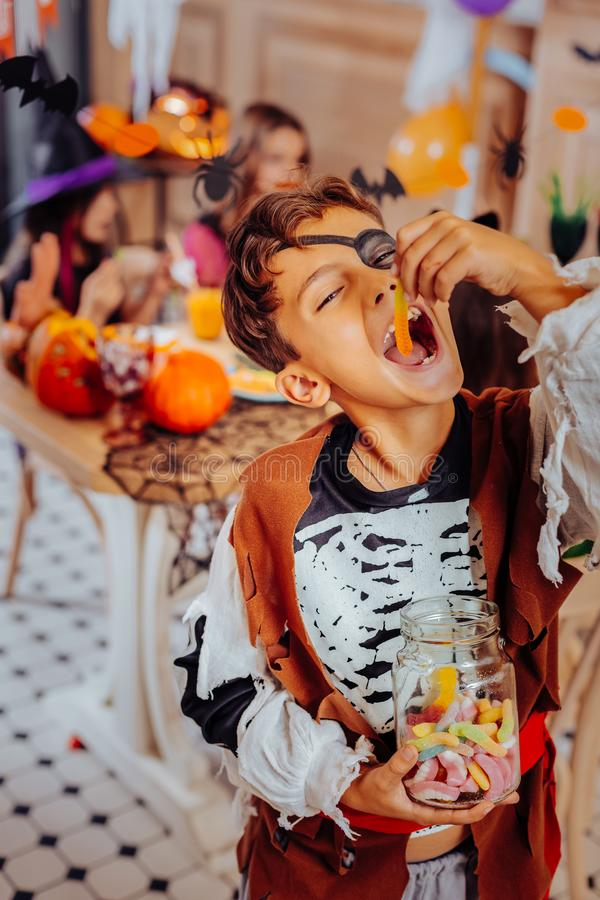 Cute schoolboy wearing nice pirate costume while attending Halloween party stock photography