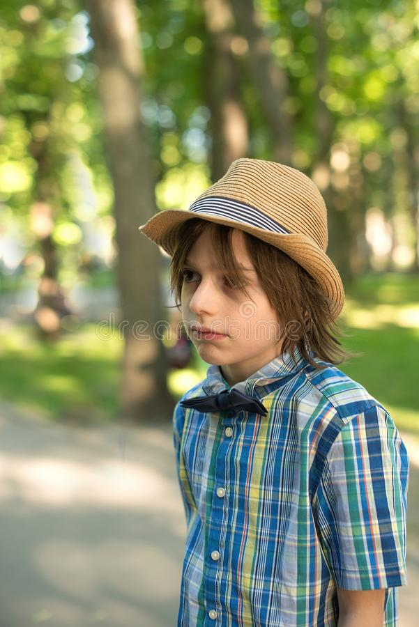 The schoolboy in a hat and tie - butterfly goes on the park. H stock images