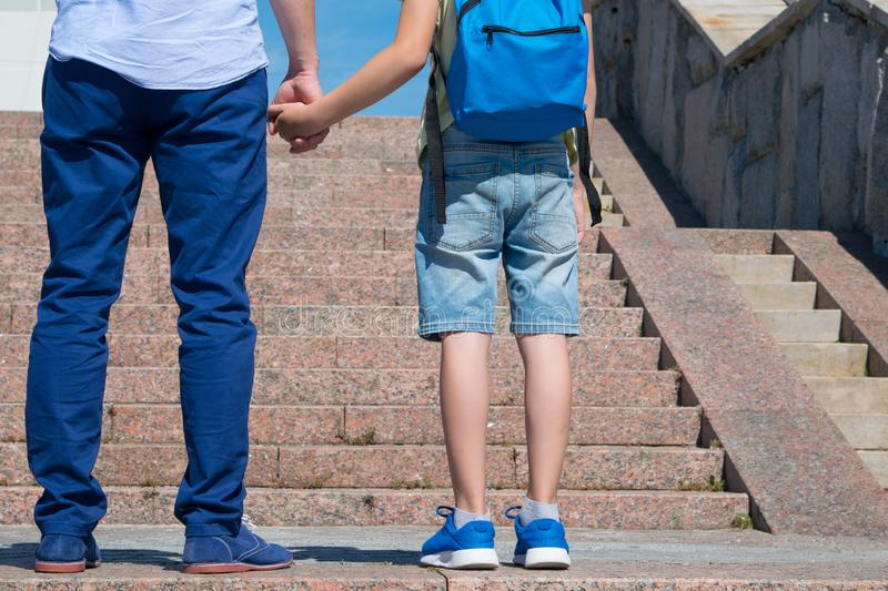 Schoolboy with his father are standing in front of the stairs upward, a boy is wearing a backpack stock photo