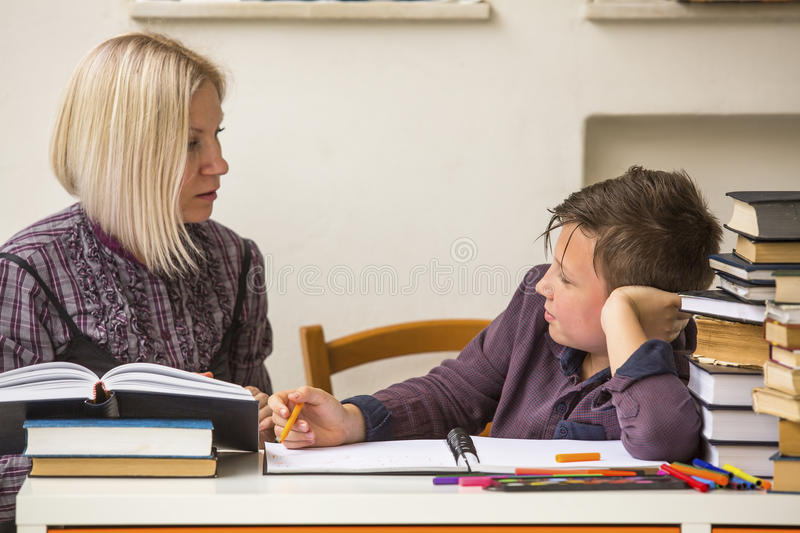 Schoolboy with his tutor do homework. Helping. stock photography