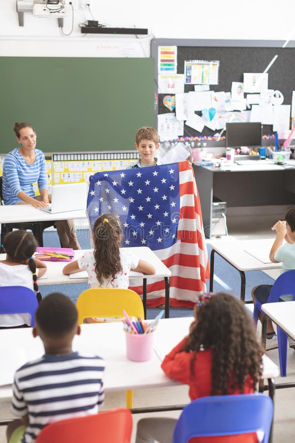 Schoolboy holding an american flag in classroom at school stock photo