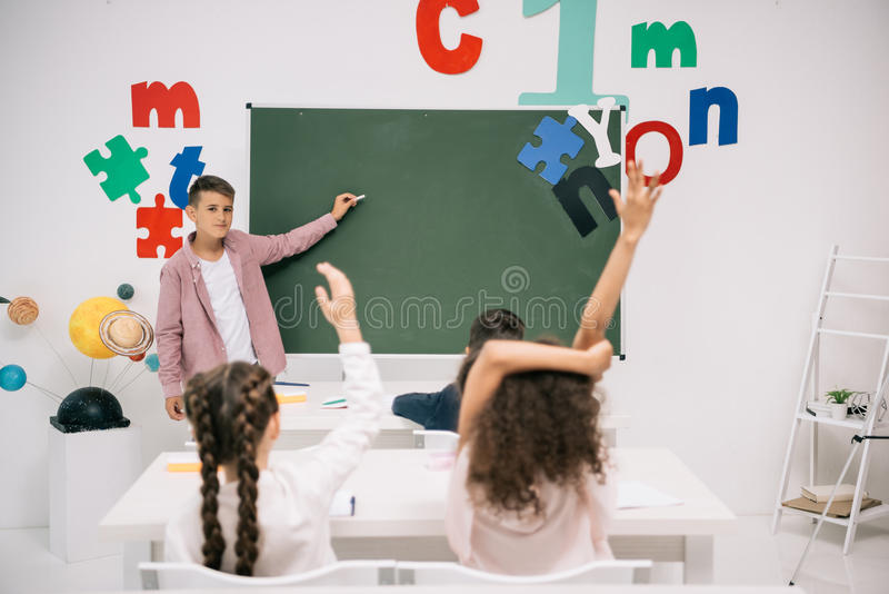 Schoolboy holding chalk and pointing at blackboard royalty free stock photo