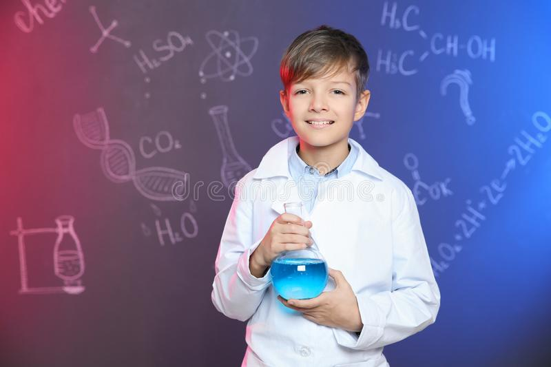 Schoolboy holding Florence flask against blackboard with written chemistry formulas stock photography