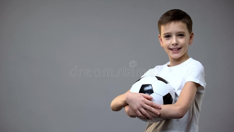 Schoolboy holding football ball and looking to camera, active leisure hobby stock images