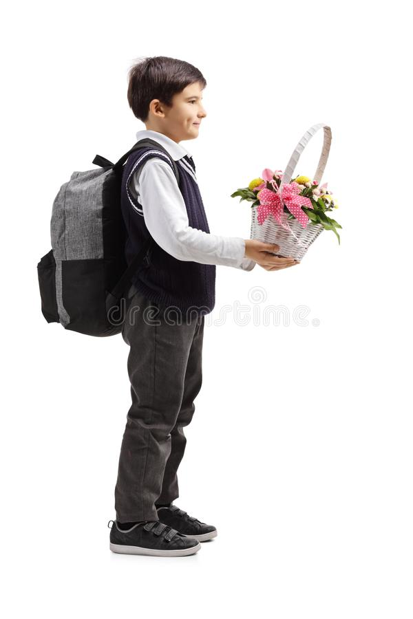 Schoolboy holding a white basket with flowers royalty free stock photo