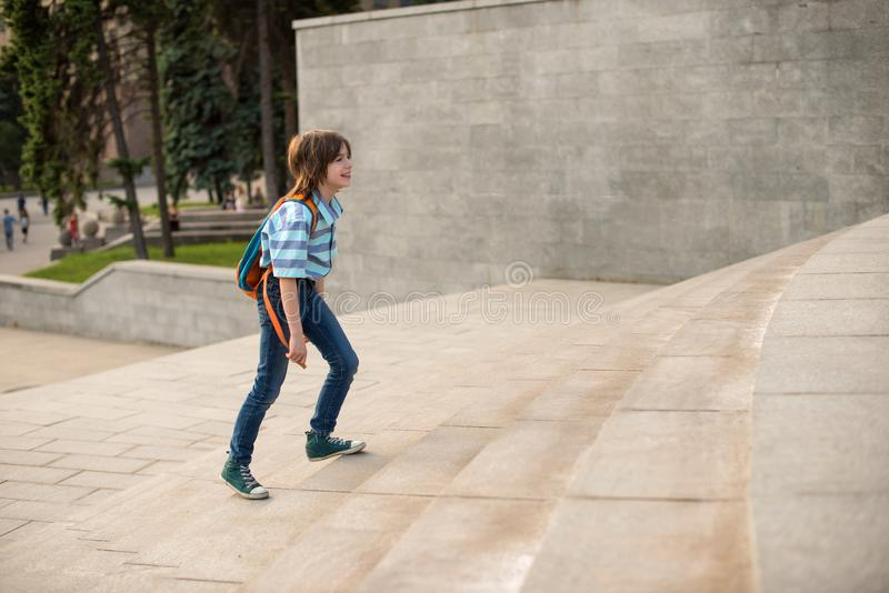 A schoolboy with a knapsack behind his back rises the steps. A schoolboy wearing strip shirt and jeans with a knapsack behind his back rises the steps royalty free stock images