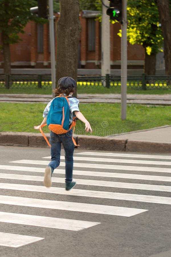 Schoolboy with a knapsack behind his back runs across the road a. Long the footpath to the green light of a traffic light, rear view royalty free stock photo