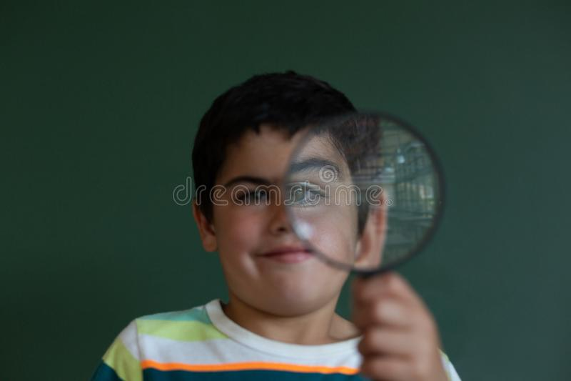 Schoolboy looking through magnifying glass in a classroom royalty free stock photos
