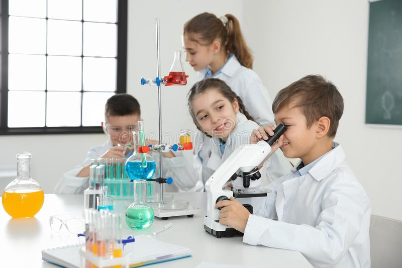 Schoolboy looking through microscope and his classmates royalty free stock photos