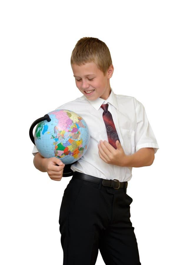 Schoolboy med jordklotet royaltyfri foto