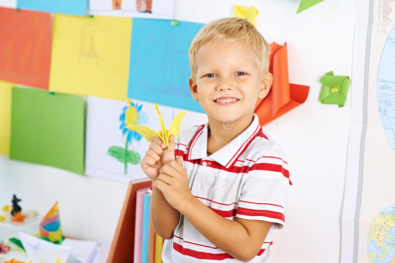 Schoolboy with a paper crane royalty free stock photos