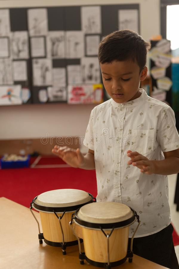 Schoolboy playing bongo in a classroom stock image