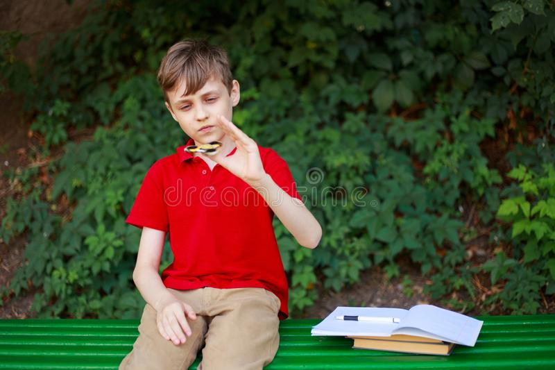 Schoolboy playing with fidget spinner instead of doing home task royalty free stock photos