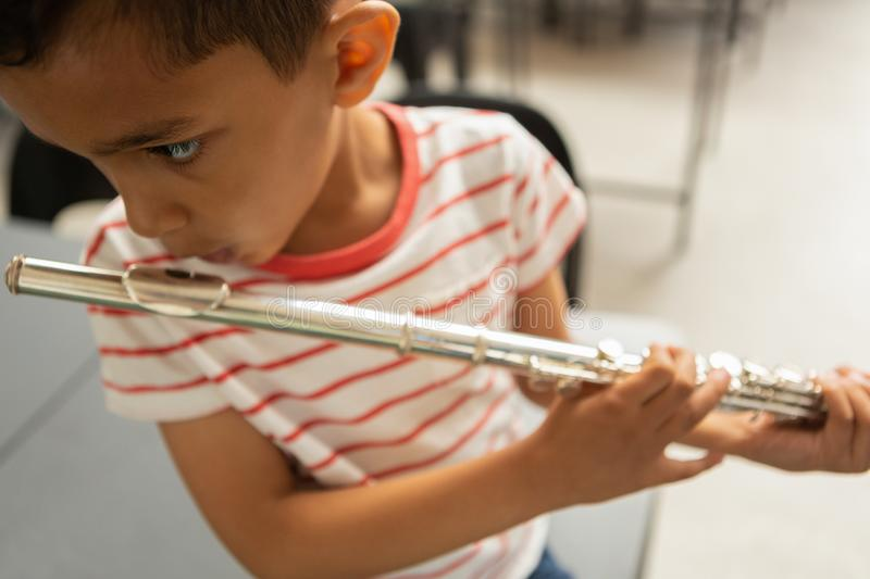 Schoolboy playing flute in a classroom royalty free stock images