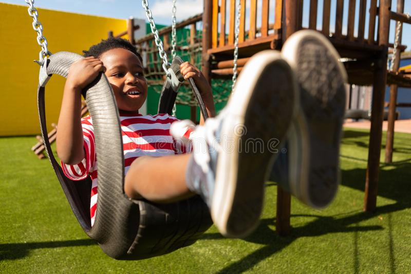 Schoolboy playing on a swing at school playground royalty free stock photo