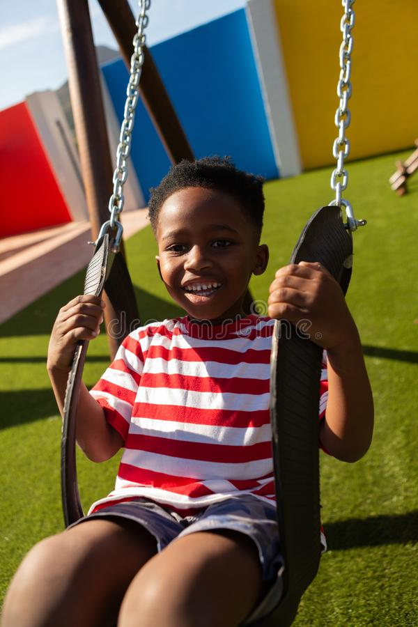 Schoolboy playing on a swing at school playground royalty free stock photography