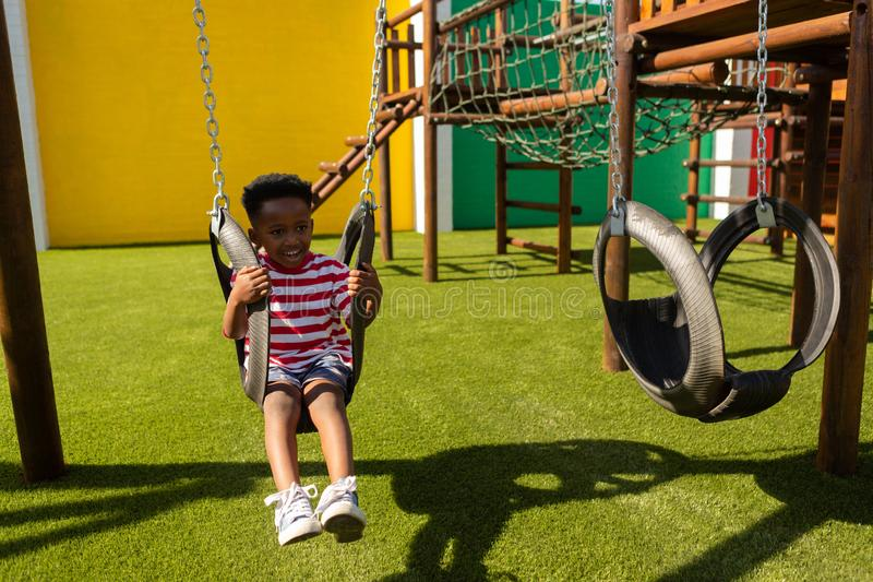 Schoolboy playing on a swing at school playground stock photo