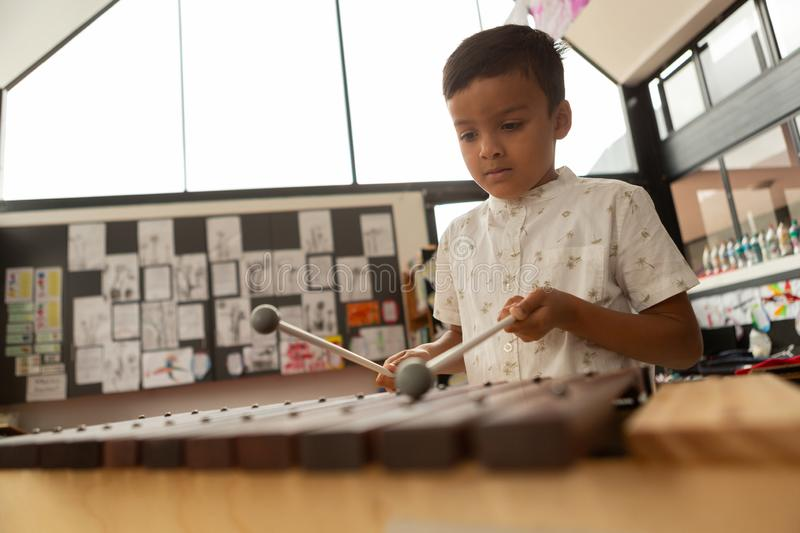 Schoolboy playing xylophone in a classroom stock photography