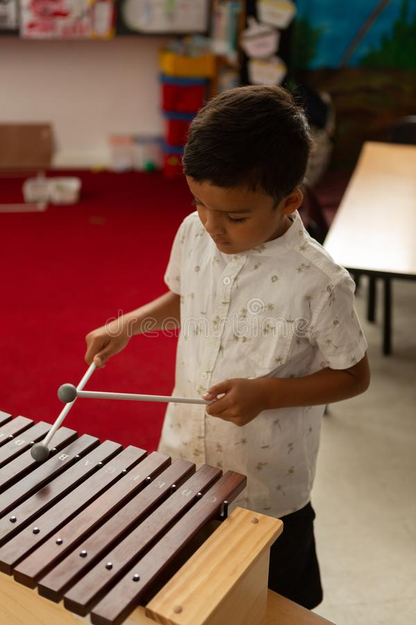 Schoolboy playing xylophone in a classroom royalty free stock photos