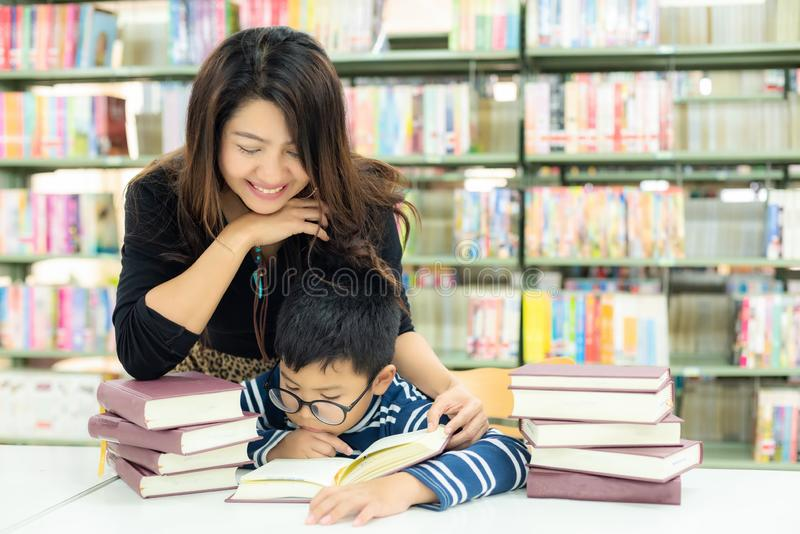 Schoolboy reading books for education and go to school with the guidance of her teacher in library . royalty free stock photo
