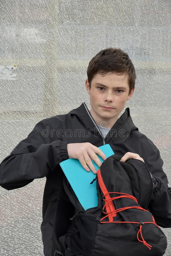 Schoolboy rummages in his rucksack, checking his books. Teenage boy at school bus stop. He rummages in his backpack and checks his schoolbooks stock photos