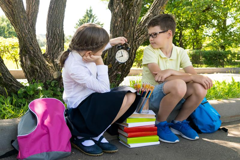 Schoolboy and schoolgirl look at the clock and wait for the lesson to begin in the park stock photos