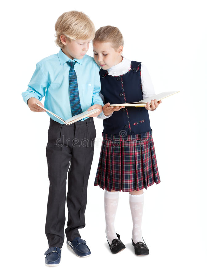 Schoolboy and schoolgirl looking at books each other, full length, isolated white background stock photos