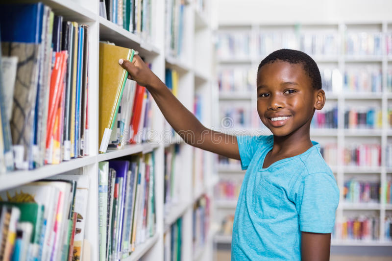 Schoolboy selecting a book from bookcase in library royalty free stock photography