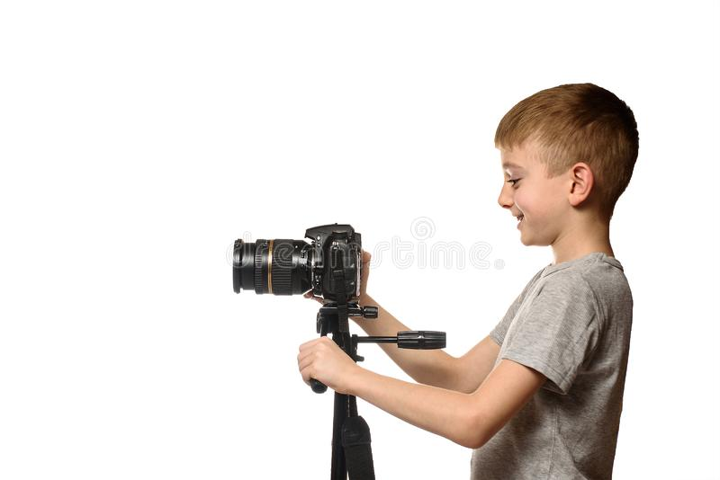Schoolboy shoots video on DSLR camera. Side view. White background, isolate royalty free stock images