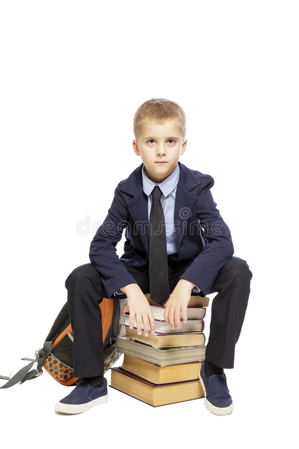 Schoolboy sitting on a big pile of books, isolated on white background. Vertical stock image