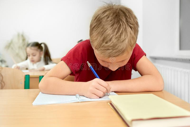 Schoolboy sitting at desk, writing with pen in copybook. Young schoolboy in red t shirt looking down, sitting at desk and writing with pen in copybook stock image