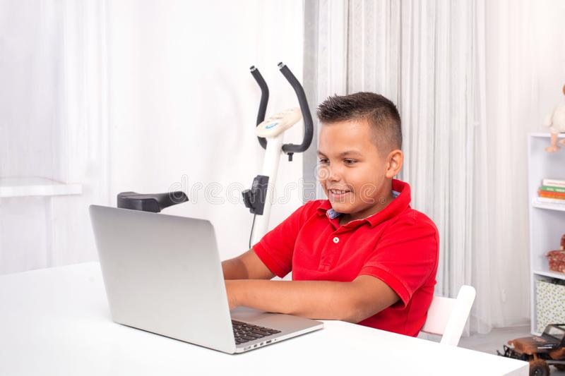 A schoolboy  is sitting at a table with a laptop in the room royalty free stock image