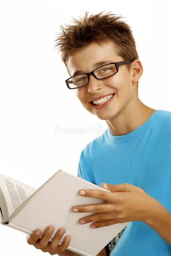 Schoolboy som läser en bok fotografering för bildbyråer