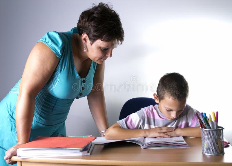 Schoolboy som studerar i klassrum med lärare royaltyfria bilder