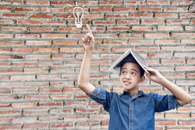 Schoolboy standing book on head and figure near stock images