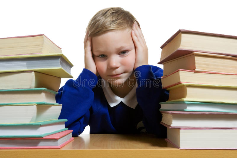 Schoolboy thinking at the desk royalty free stock image