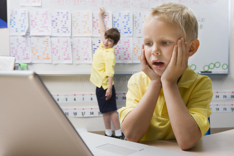 Schoolboy Using A Laptop. Shocked little boy looking at laptop with classmate writing on whiteboard in classroom royalty free stock images